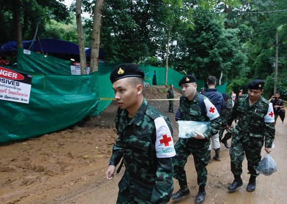 Rettungskräfte des thailändischen Militärs begeben sich zum abgesperrten Eingang der Höhle.