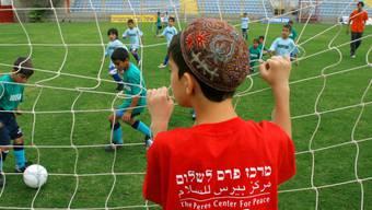Ein israelischer Junge aus der südlichen Stadt Sderot schaut israelischen und palästinensischen Kindern bei einem gemeinsamen Fussballturnier in Herzliya, nördlich von Tel Aviv zu (Symbolbild)