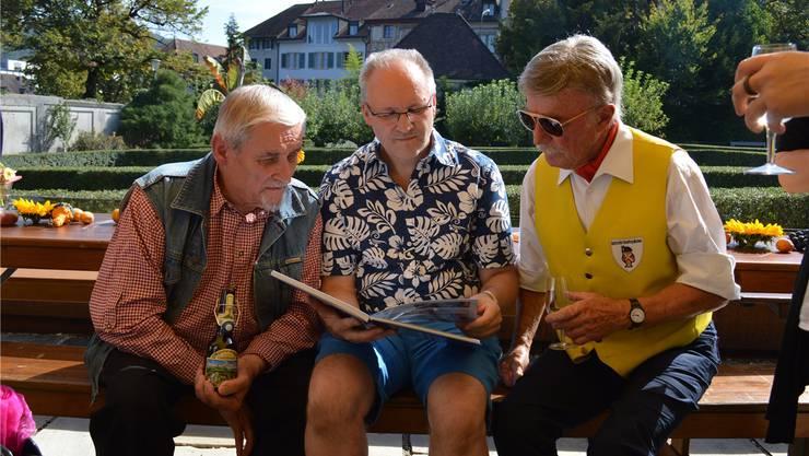 Manfred Lässig senior, Manfred Lässig junior und Gusti Beer (von links) ganz vertieft ins Jubiläumsbuch.