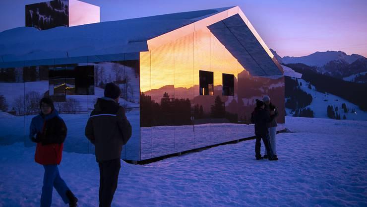 Spaziergänger auf dem Winterwanderweg zwischen Gstaad und Schönried sehen sich die Installation des amerikanischen Küstlers Doug Aitken an.