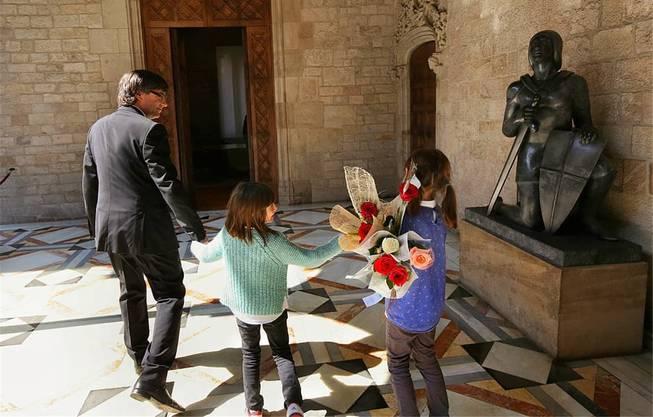 Carles Puigdemont und seine Töchter Magali und Maria im Palast der katalanischen Regionalregierung in Barcelona. Am Tag der Frau im Jahr 2016 erhielten sie Blumen. Die kniende Statue steht für den katalanischen Nationalheiligen Sankt Georg.