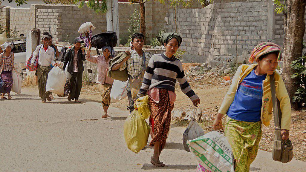 Fliehende tragen ihre Habseligkeiten aus der umkämpften Stadt Laukkai im Nordosten Myanmars.
