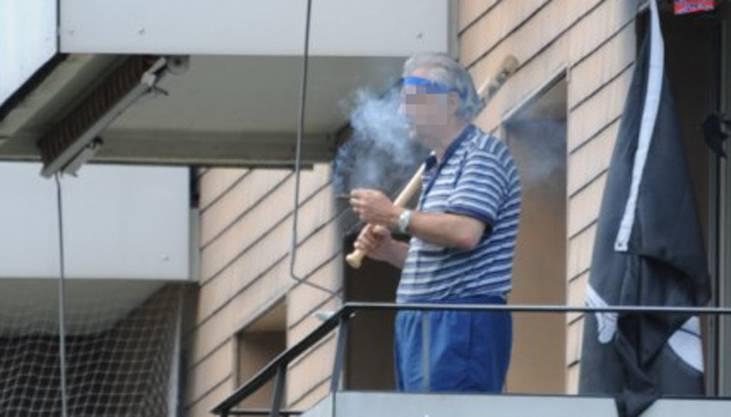 Seelenruhig pafft er auf seinem Balkon