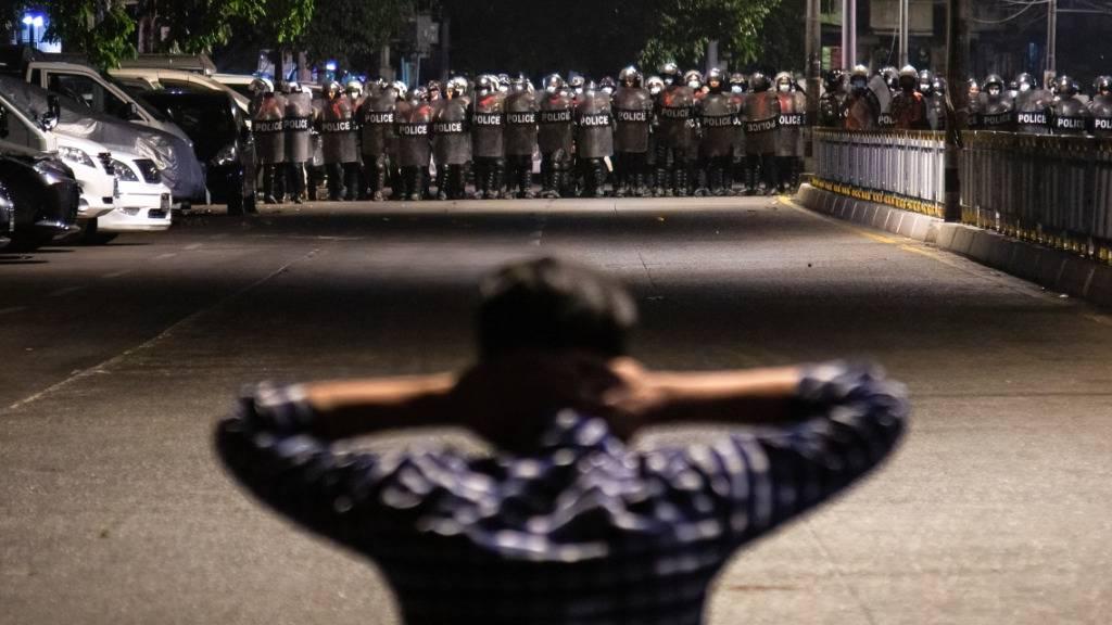 Ein Demonstrant steht auf einer Straße vor einer Reihe von Polizisten. Im Land Myanmar ist es zu Zusammenstößen zwischen Anhängern der Militärjunta und Teilnehmern einer Pro-Demokratie-Kundgebung gekommen. Foto: Theint Mon Soe/SOPA Images via ZUMA Wire/dpa
