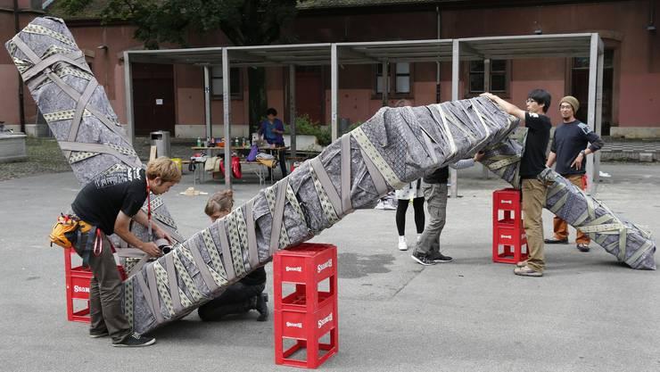 Der japanische Performancekuenstler und Architekt Noriyuki Kiguchi (mit rotem Megaphon) treibt mit seiner Crew und Passanten ein riesiges Schlangengebilde durch den Kopfbau der Kaserne vom Kasernenareal zum Rhein