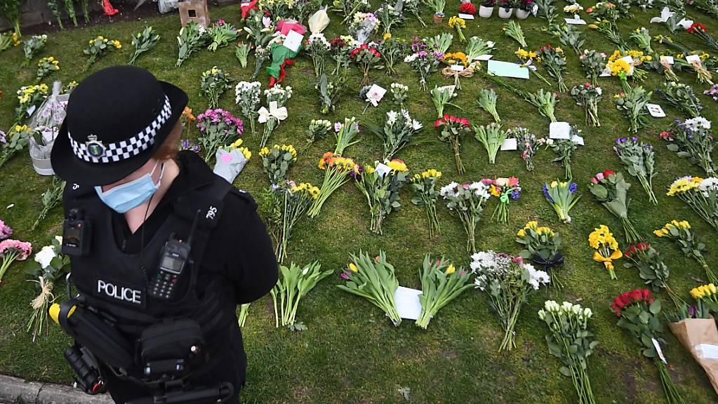 dpatopbilder - Eine Polizistin steht vor einer Grünfläche vor Schloss Windsor, auf der Blumen für den verstorbenen Philip abgelegt wurden. Foto: Victoria Jones/PA Wire/dpa