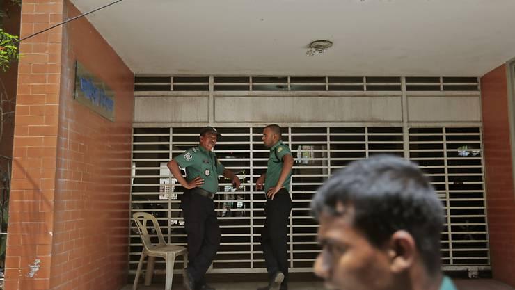 Zwei Polizisten bewachen das Gebäude, in welchem die beiden Homosexuellen-Aktivisten Ende April getötet wurden. (Archiv)