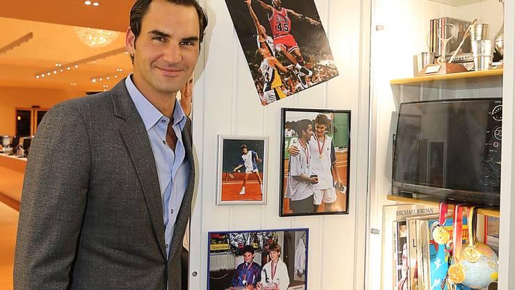 Roger Federer posiert vor dem Garderobenschrank, in welchem viele persönlichen Gegenstände des Tennisstars ausgestellt sind.