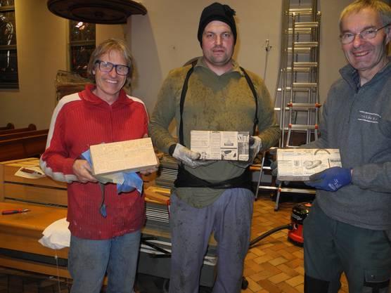 Kurt Bangerter, Andreas Burri und Christoph Trüssel (v.l.n.r.) von Metzler Orgelbau zeigen die in Zeitungspapier von 1935 eingewickelten Backsteine.