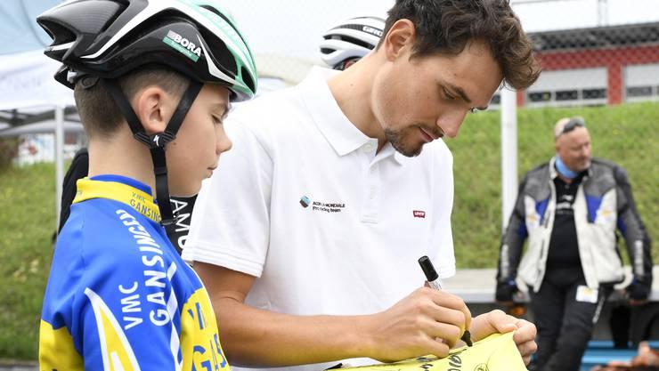 Silvan Dillier gibt einem Junior vom VMC Gansingen ein Autogramm.