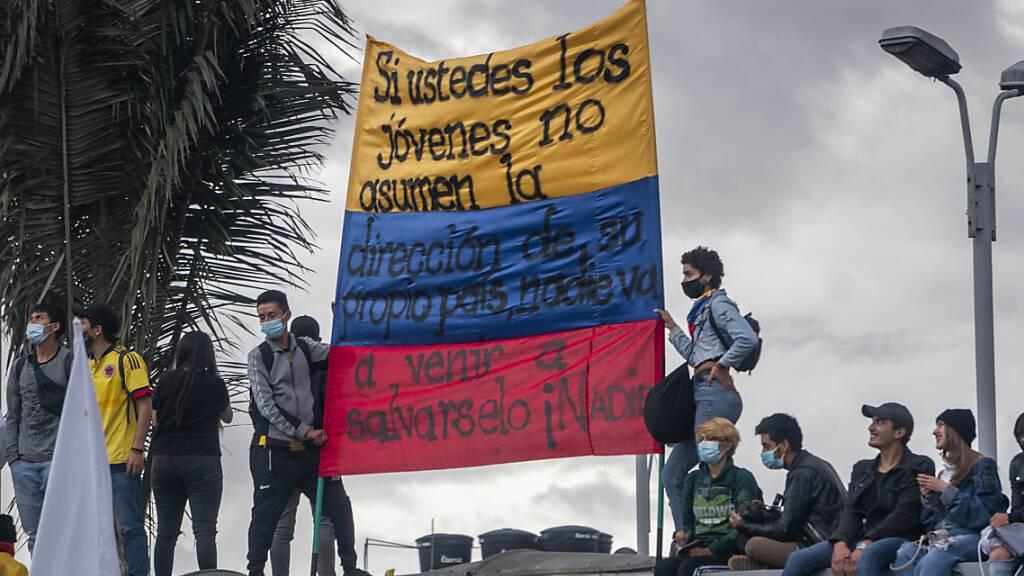 Menschen tragen eine kolumbianische Flagge, auf der geschrieben steht: «Wenn ihr jungen Leute nicht die Führung eures eigenen Landes übernehmt, wird niemand kommen, um euch zu retten, niemand». Foto: Daniel Garzon Herazo/ZUMA Wire/dpa
