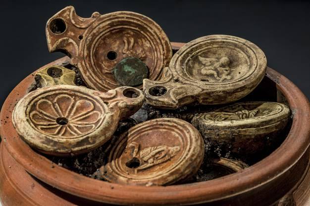 ...entpuppt sich bald als aussergewöhnlichen Fund: Im Innern sind 22 Öllampen mit Bronzemünzen darauf vorzufinden.
