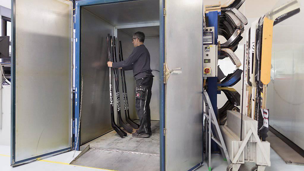 In Handarbeit wird im Jura der einzige Schweizer Eishockeystock hergestellt. Hier stellt ein Mitarbeiter der Firma Busch einige Stücke in einen Ofen, in dem diese während acht Stunden bei 70 bis 80 Grad «gebacken» werden.