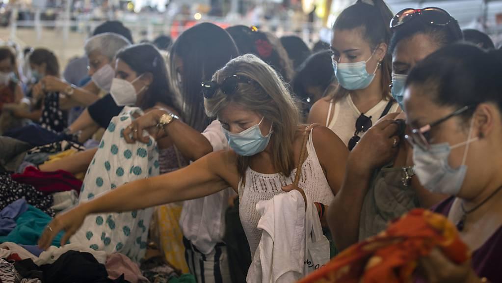 Kundinnen, die Mundschutz tragen, kaufen Kleidung an einem Stand auf einem Markt in Barcelona. Die spanische Region Katalonien führt eine ungewöhnlich strenge Maskenpflicht ein.