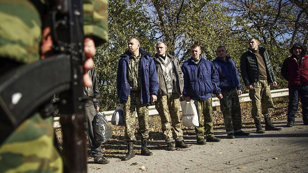 Ukrainische Soldaten warten - bewacht von prorussischen Rebellen - auf einen Gefangenenaustausch der Konfliktparteien in der Ostukraine.