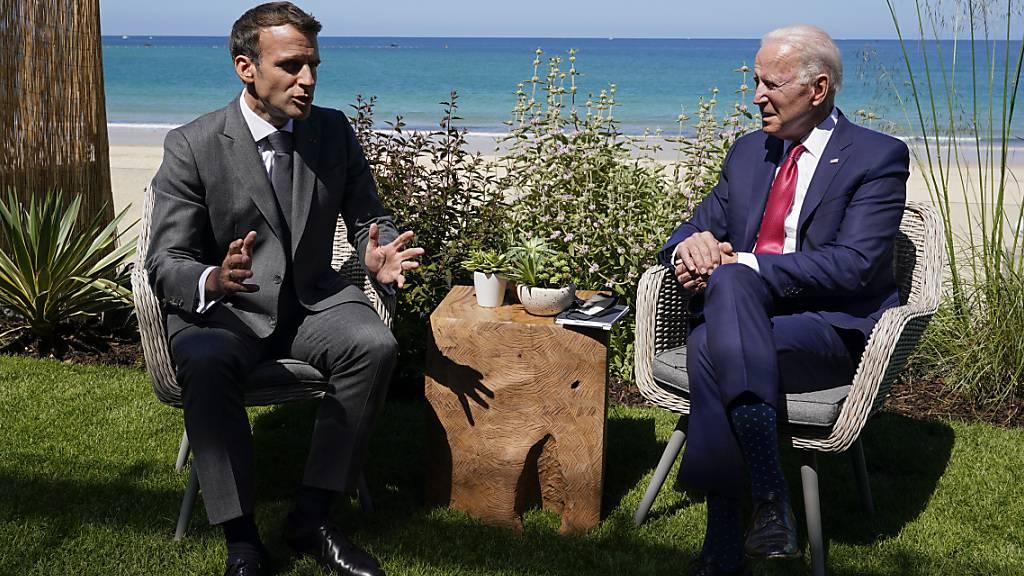 Joe Biden (r), Präsident der USA, und Emmanuel Macron, Präsident von Frankreich, unterhalten sich bei einem gemeinsamen Treffen während des G7-Gipfels. Foto: Patrick Semansky/AP/dpa