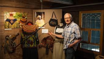 Christoph Haller, Präsident der Museumskommission, in der Sonderausstellung «Handwerkskunst» vor dem prächtigen Festgewand eines hochgestellten Kameruners und einer Aargauer Sonntagstracht. bkr