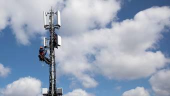 Ein Techniker rüstet eine Mobilfunkantenne mit 5G-Elementen aus.