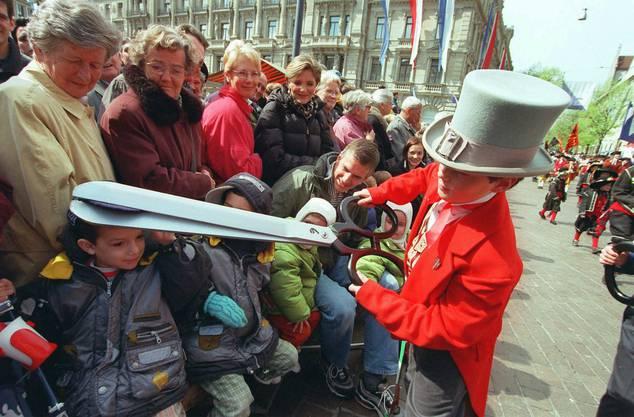 Ein als Schneider verkleideter Junge bearbeitet am traditionellen Sechseläuten-Kinderumzug auf dem Zürcher Paradeplatz die Kappe eines kleinen Zuschauers.