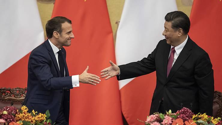 """Der französische Präsident Emmanuel Macron (l) und der chinesische Staatschef Xi Jinping warnen in einem gemeinsamen Papier, dass """"der Verlust biologischer Vielfalt und der Klimawandel weltweit den Frieden und die Stabilität bedrohen""""."""