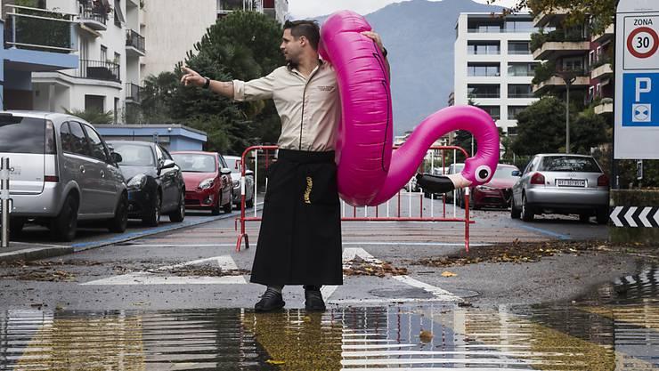 Ein Kellner der Lungolago-Pizzeria watet mit einem rosa Flamingo über die überschwemmte Strasse in Locarno.