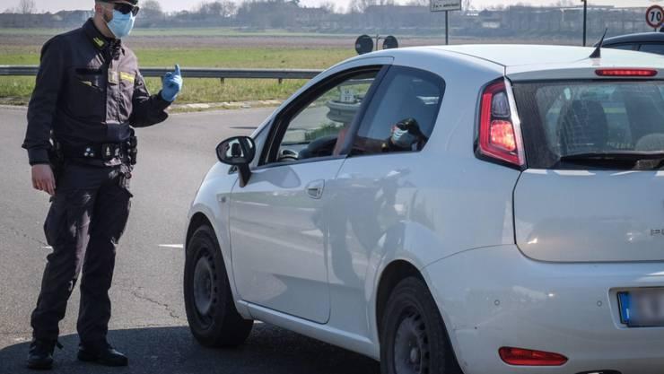 Ein Polizist stoppt ein Auto beim Ort Casalpusterlengo, der wegen des Coronavirus abgeriegelt ist.