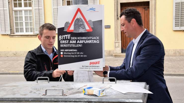 Reto Wettstein (r.) und Sandro Graf hängen das erste Informationsplakat auf.