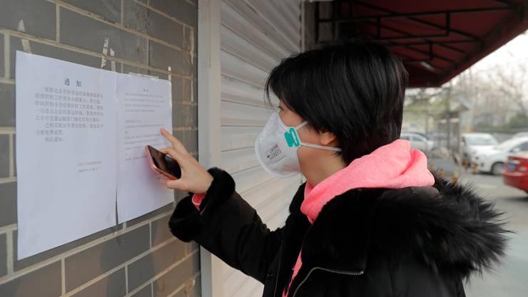 Eine Chinesin liest die Anordnungen der Regierung zum Coronavirus in einer Bus-Station in Peking. (Bild: Keystone)