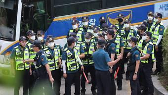 dpatopbilder - Polizeibeamte stehen in Seoul zusammen, um nach dem als vermisst gemeldeten Bürgermeister Park Won Soon zu suchen. Foto: Kim Ju-Sung/Yonhap/AP/dpa
