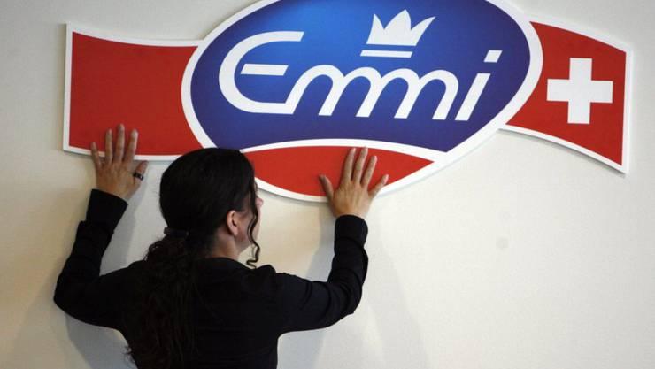 Emmi verkauft die Frisch-Service AG: Eine Mitarbeiterin des Milchverarbeiters befestigt das Logo des Unternehmens an einer Wand (Archivbild).