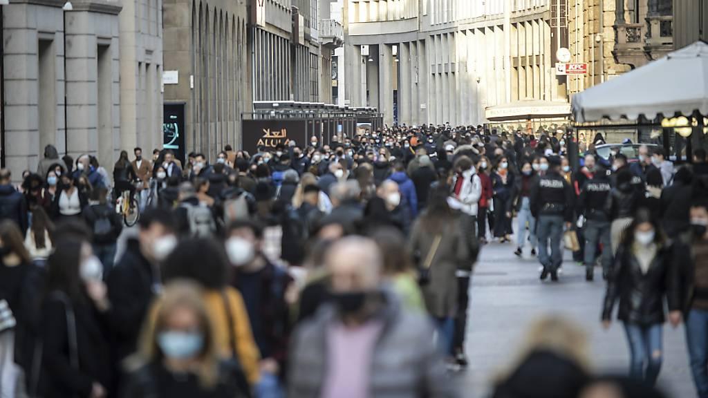 Menschen schlendern durch die Innenstadt. Von Montag an gilt für Millionen Menschen in Italien wieder ein strikter Lockdown. Regionen wie Latium mit der Hauptstadt Rom, die Lombardei mit Mailand, Piemont, Venetien oder die Emilia-Romagna werden zu sogenannten roten Zonen.