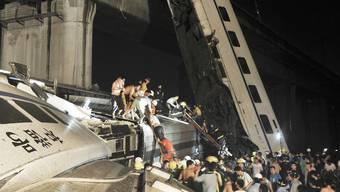 Rettungskräfte bergen Passagiere aus dem verunfallten Zug in China