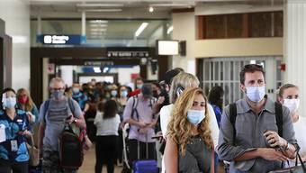 Reisende an einem Flughafen auf Hawaii tragen Mund-Nasen-Schutz. Foto: Marco Garcia/AP/dpa
