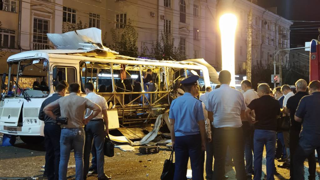 Ein ausgebrannter Kleinbus steht auf einer Straße. Bei der Explosion des Busses sind zwei Menschen ums Leben gekommen. 18 weitere seien in der Nacht verletzt worden.