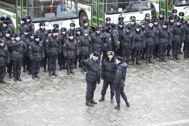 """Polizisiten """"bewachen"""" den Trauermarsch der Putin-Kritiker."""