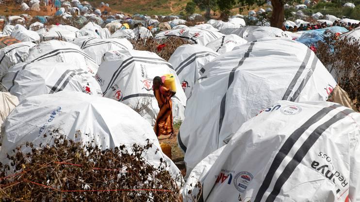 Ein Mädchen aus Eritrea trägt Wasser zu ihrem Zelt.