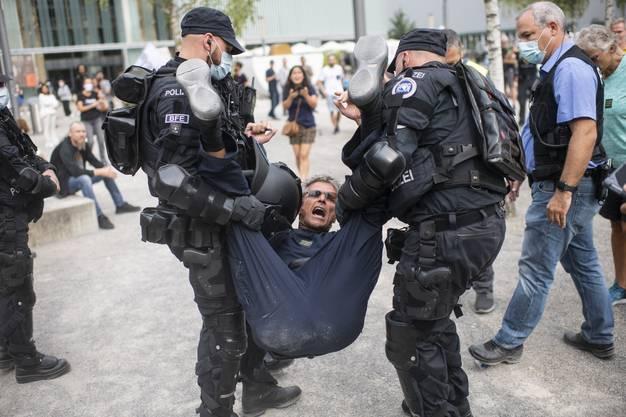 Die Polizei führt an der Demo einen Teilnehmer ab.