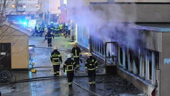 Feuerwehrleute vor der ausgebrannten Moschee in Eskilstuna