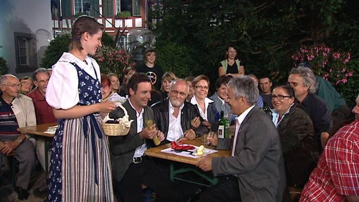 Kreativität gefragt: «SF bi de Lüt»-Moderator Nik Hartmann (vorne links am Tisch) übergibt Rolf Alder von der Brugger Delegation (vorne rechts) die Wochenaufgabe.