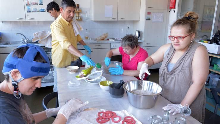 Die Bewohnerinnen und Bewohner bereiten in der Küche Einmachgläser vor.