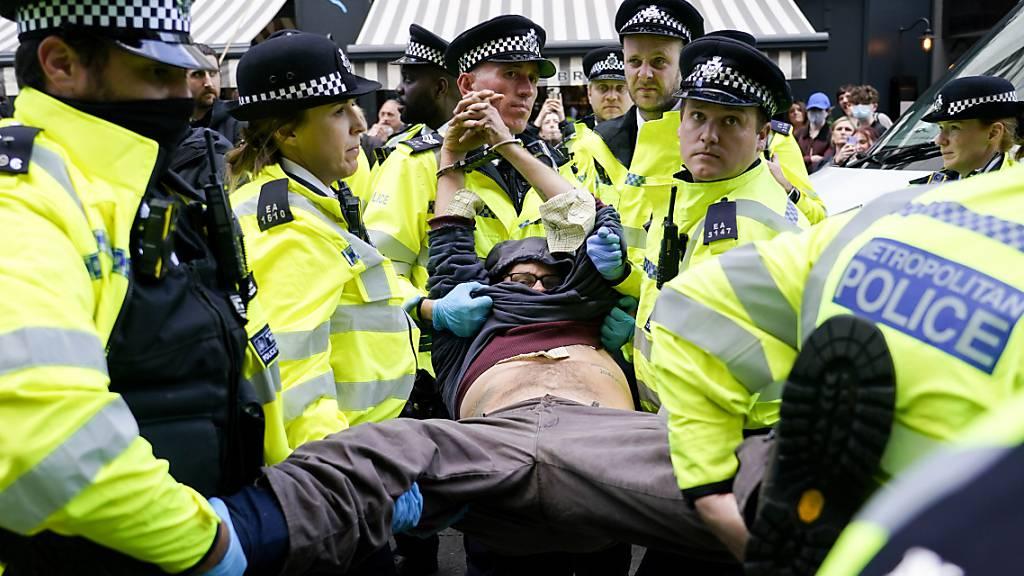 Polizisten verhaften einen Demonstranten, der sich während eines von der Umweltschutzbewegung Extinction Rebellion organisierten Protests unter einen Lieferwagen klebte. Bei der Protestaktion in London laut Mitteilung von Scotland Yard am späten Montagabend mehr als 50 Menschen festgenommen worden. Foto: Alberto Pezzali/AP/dpa