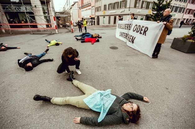 Dabei stellen sich Aktivisten tot auf dem Boden.