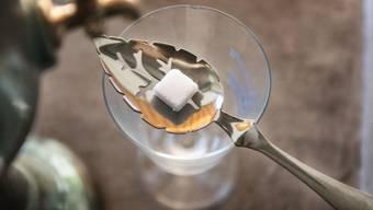 Mit Zucker auf einem Silberlöffel wird Absinth korrekt zubereitet