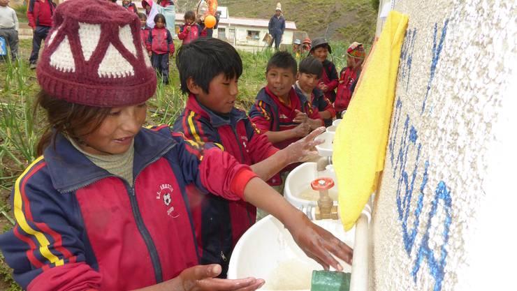 Händewaschen für eine bessere Gesundheit. Bolivianische Kinder erfreuen sich an der neuen Anlage.