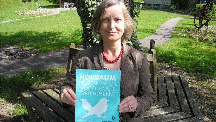 Carmen Röser präsentiert die hellblaue Hörtafel im Park des Wohnzentrums Frankenthal.