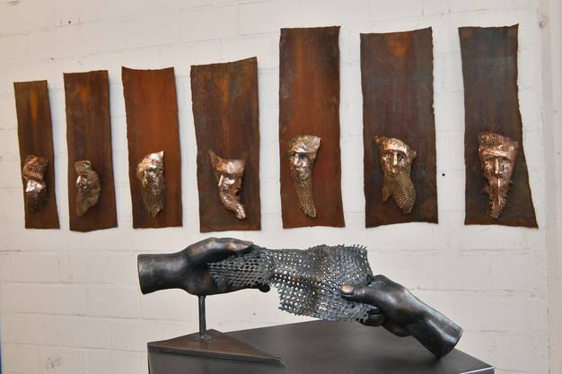 """""""Gefangen in der Zeit"""" heisst das Werk im Vordergrund. Hinten sind Gesichter zu erkennen. Beides stammt von Oliviero Gorza."""