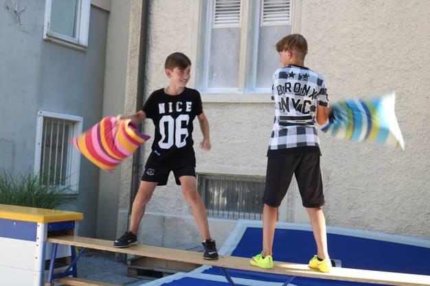 Die beiden Jungs versuchen, einander mit Kissen von der Bank runter auf die Matte zu schubsen. Wer wohl zuerst herunterfällt?
