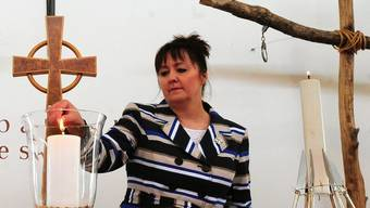Eine Hinterbliebene zündet die Kerze zum Gedenken des Falklandkriegs