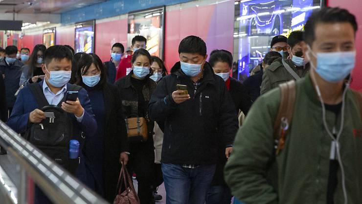 ARCHIV - Pendler schauen auf ihre Smartphones, während sie durch eine U-Bahn-Station in Peking gehen. Gut ein Jahr nach dem Ausbruch gilt das Coronavirus in China als so gut wie besiegt. Selbst in der besonders betroffenen Metropole Wuhan ist von Krise kaum noch etwas zu spüren. Foto: Mark Schiefelbein/AP/dpa