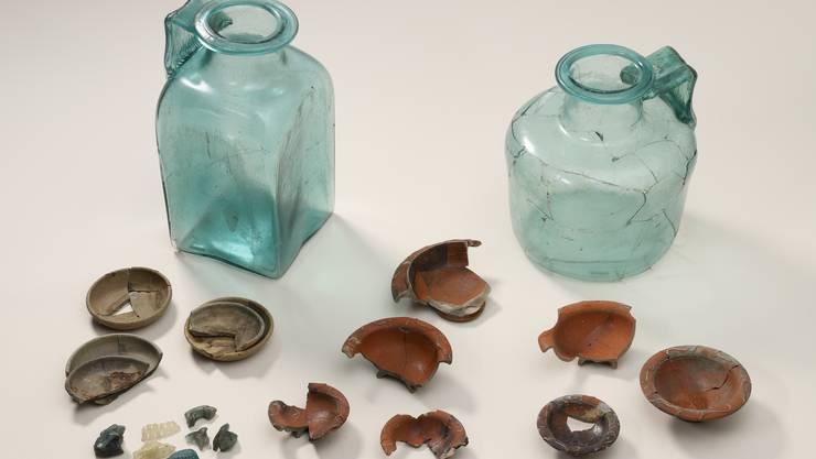 Die Glasurnen aus Flumenthal und eine Auswahl der Beigaben aus den beiden Brandgräbern.